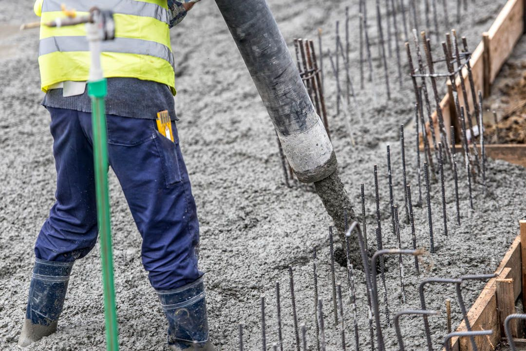 Contruction worker pouring concrete, directing the pump tube